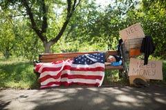 Mening van een dakloze mens die die op bank liggen met de vlag van de V.S. wordt behandeld Stock Afbeeldingen