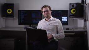 Mening van een gelukkige en nadenkende programmering, beambte, die op zijn plaats bevroor In zijn handen, laptop, en hij zit stock videobeelden