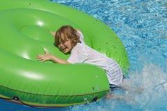 Mening van een jongen 7 die van de kant van de pool op een groen opblaasbaar bed in het water springen stock fotografie
