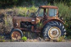 Mening van een oude geroeste die tractor in aard wordt geparkeerd stock foto