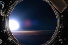 Mening van een patrijspoort van ruimtestation op de Aardeachtergrond Stock Afbeeldingen