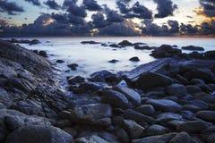 Mening van een rotsachtige kust bij schemer Stock Fotografie