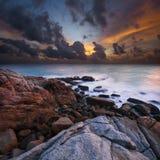 Mening van een rotsachtige kust bij zonsondergang Stock Foto's
