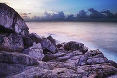 Mening van een rotsachtige zeekust bij schemer. Stock Foto's
