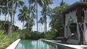 Mening van een tropische tuin met de pool en bergen tegen de achtergrond van de blauwe hemel in zonnige dag, Bali, Indonesië stock videobeelden
