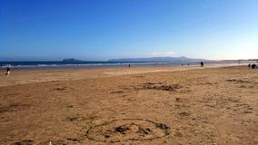 Mening van een zandig strand met mensen en eiland op de achtergrond Royalty-vrije Stock Afbeeldingen