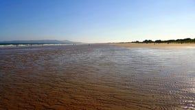 Mening van een zandig strand met mensen en eiland op de achtergrond Royalty-vrije Stock Fotografie