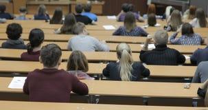 Mening van erachter van een grote gemengde het behoren tot een bepaald rasgroep studenten in een klaslokaal, Studenten geinteress stock videobeelden