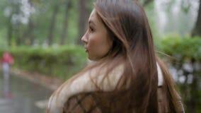 Mening van erachter van een modieus jong meisje die in geruite bruine laag buiten in daling lopen stock footage