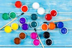 Mening van gekleurde verf met borstels op een blauwe houten achtergrond Royalty-vrije Stock Foto's