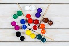 Mening van gekleurde verf met borstels op een witte houten achtergrond Stock Foto's