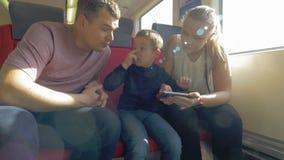 Mening van gelukkige familie in de spoorwegreis die smartphone, Praag, Tsjechische Republiek gebruiken stock footage