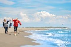 Mening van gelukkige jonge familie die pret op het strand hebben Stock Foto