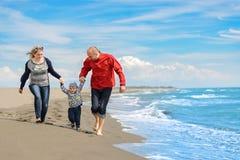 Mening van gelukkige jonge familie die pret op het strand hebben Stock Foto's
