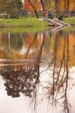 Mening van herfstpark met mensen en bomenbezinning in het water Royalty-vrije Stock Foto's