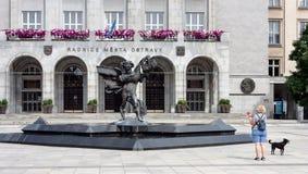 Mening van het beeldhouwwerk met fontein die van Icarus en vrouw met hond, zich vóór voorgevel van de gemeentestad bevinden van O stock foto