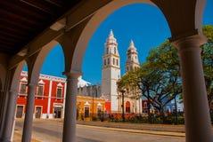 Mening van het belangrijkste Park door de boog van het bibliotheekgebouw in Campeche, Mexico Op de achtergrond is de kathedraal d royalty-vrije stock afbeelding