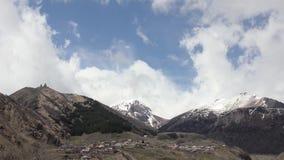 Mening van het bergdorp en de tempel van de Heilige Drievuldigheid Gergeti in de bergen op een achtergrond van het witte wolken d stock videobeelden