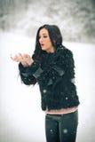 Mening van het gelukkige donkerbruine meisje spelen met sneeuw in de winterlandschap Mooi jong wijfje op de winterachtergrond Aan Royalty-vrije Stock Afbeelding