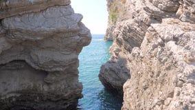 Mening van het lagune azuurblauwe duidelijke overzees door een rotsachtige smalle doorgang stock video