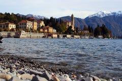 Mening van het meer, een jacht en een dorp op de achtergrond van de bergen Royalty-vrije Stock Afbeeldingen