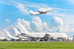 Mening van het parkeren van luchthavenvliegtuigen bij de terminal, en een vliegtuig die in de hemel met wolken van start gaan Stock Foto's