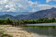 Mening van het reservoir van Manzanares el Real waar u een brug en op de achtergrond kunt zien de grote bergen van La Pedriza Stock Afbeelding