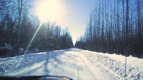 Mening van het venster van een bewegende auto op een de winter sneeuwweg door het bos, de winter in Rusland stock videobeelden