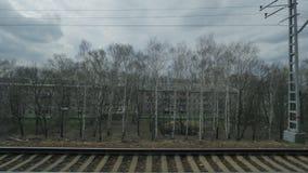 Mening van het venster van een bewegende trein gezien bomen, gebouwen, bruggen en spoorweg stock videobeelden
