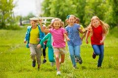 Mening van het vliegtuigstuk speelgoed en jonge geitjes van de meisjesholding erachter royalty-vrije stock afbeelding