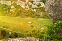 Mening van hierboven aan de vallei onder de bergen Tenten op het groene gras Royalty-vrije Stock Fotografie