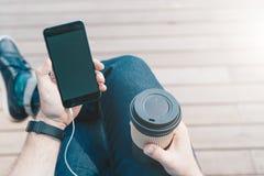 Mening van hierboven Close-up van smartphone met het lege scherm en kop van koffie in handen van de zitting van de hipstermens royalty-vrije stock foto