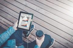 Mening van hierboven Close-up van tabletcomputer met het zwarte lege scherm en kop van koffie in handen van de zitting van de hip royalty-vrije stock foto