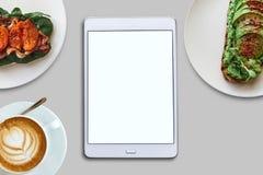 Mening van hierboven In het midden is een tablet met het leeg scherm voor tekst Naast hem een verscheidenheid van voedsel en koff stock foto's