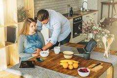 Mening van hierboven Jong echtpaar in keuken De zwangere vrouw zit bij lijst, houdt de mens haar zwangere buik stock afbeelding