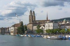 Mening van historisch de stadscentrum van Zürich met Grossmunster-Kerk en Limmat-rivier Zeemeeuw in de hemel royalty-vrije stock foto