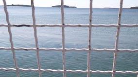 Mening van ijzeromheining met blauwe overzees op achtergrond Veiligheidsnet die overzees, close-up overzien stock videobeelden