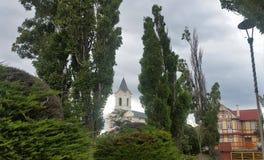 Mening van kerktorenspits en de tudor-Stijl bouw met decoratieve helft-betimmert en evergreens in Puerto Natales, Patagonië Chili Stock Foto