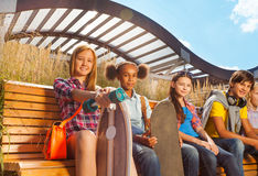 Mening van kinderen die samen op houten bank zitten Stock Afbeeldingen