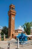 Mening van klokketoren van bakstenen en een het glasbeeldhouwwerk van de stervorm in Murano wordt gemaakt die Stock Afbeelding