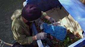 Mening van landloper het graven in vuilnisbak stock videobeelden