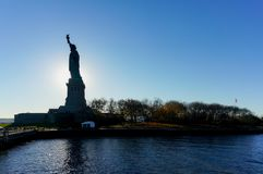 Mening van Liberty Statue-silhouet dichtbij zonsonderganguur royalty-vrije stock afbeelding