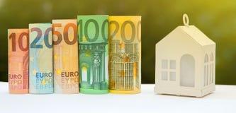Mening van muntstukstapel met huismodel op groene achtergrond, besparingen stock foto's
