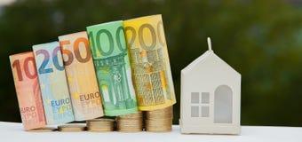 Mening van muntstukstapel met huismodel op groene achtergrond, besparingenplannen voor huisvesting, financieel concept, Hypotheek stock afbeelding