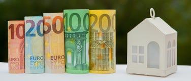 Mening van muntstukstapel met huismodel op groene achtergrond, besparingenplannen voor huisvesting, financieel concept, Hypotheek royalty-vrije stock afbeelding