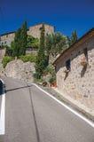 Mening van muur, oude huizen en kerk dichtbij weg in het Toscaanse platteland Royalty-vrije Stock Afbeelding