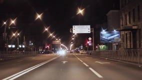 Mening van nachtstad en weg Camera binnen het drijven van auto kruispunt stock footage