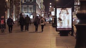 Mening van nachtstraat in stad met lopende mensen en het advertentiescherm stock videobeelden