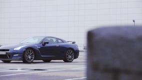 Mening van nieuwe donkerblauwe autotribune op leeg parkeren Het model van het presentatiemerk koplampen Koude schaduwen stock footage