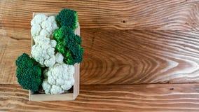 Mening van organische broccoli en bloemkool in de doos Seizoengebonden lokaal de opbrengsconcept van het oogstgewas Authentiek Le royalty-vrije stock afbeeldingen